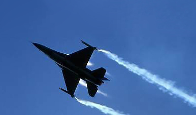 F-16 Fighting Falcon with wingtip smoke generators and vortex contrails.